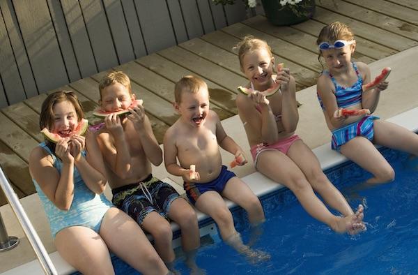 kids smiling by concrete pool